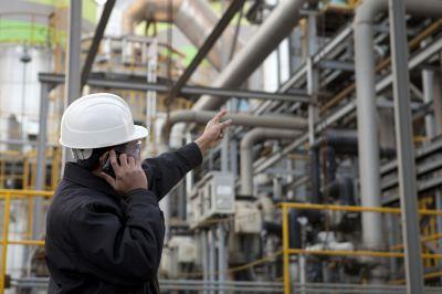 Homem com capacete de segurança se comunica via celular e aponta em direção a tubulações em ambiente industrial