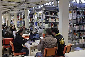Foto da parte interna da biblioteca - estantes e mesa com alunos